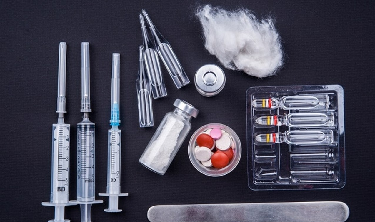 grouping of steroid drugs in syringes and tablets black background