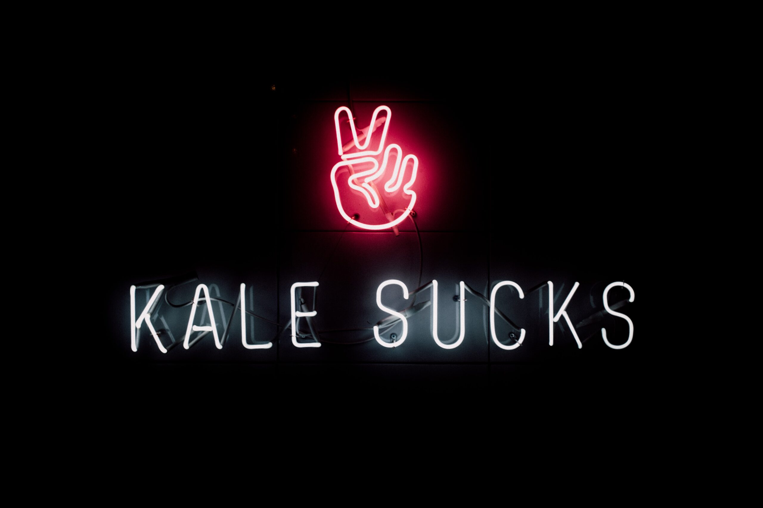 neon sign that reads Kale Sucks